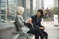 Businessman and businesswoman drinking coffee and talking on urban bench - HEROF06264