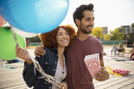 Affectionate young couple with popcorn and balloons in park - HEROF06291