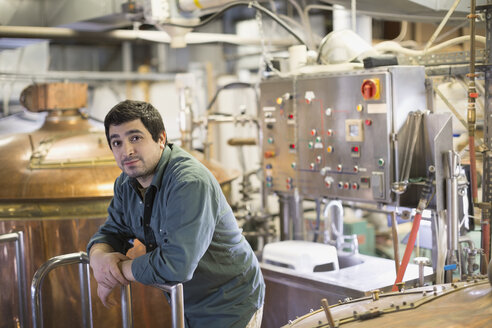 Portrait of confident brewery worker near copper stills - HEROF06462