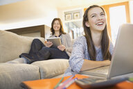 Mother and daughter using technology in living room - HEROF06498