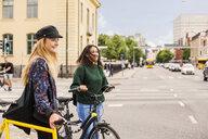 Two young women pushing bikes in town - ASTF02473