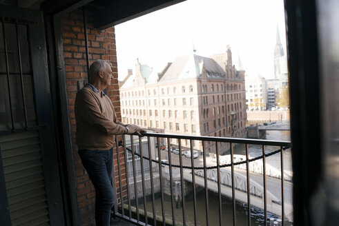 Germany, Hamburg, Speicherstadt, senior businessman standing at the window with view over the city - JOSF02887