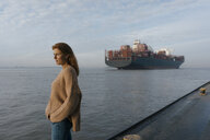 Germany, Hamburg, woman standing on pier at the Elbe shore with container ship in background - JOSF02893
