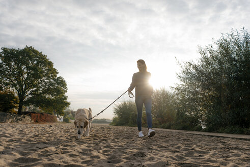 Germany, Hamburg, woman walking with dog on beach at the Elbe shore - JOSF02896