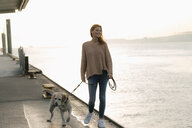 Germany, Hamburg, woman walking with dog on pier at the Elbe shore - JOSF02902