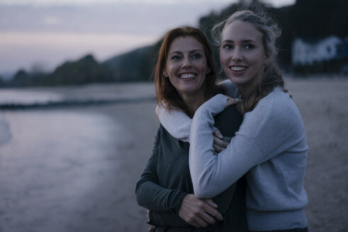 Germany, Hamburg, happy mother and teenage girl hugging on the beach at Elbe shore in the evening - JOSF02920