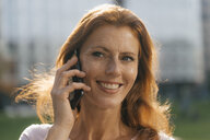 Portrait of smiling businesswoman on cell phone outdoors in the city - JOSF02935