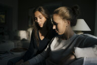 Two teenage girls using cell phone on couch at home - JOSF02941