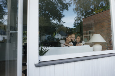 Happy mother with two teenage girls on couch at home behind windowpane - JOSF02950