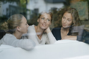 Mother with two teenage girls on couch at home behind windowpane - JOSF02953