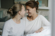 Happy mother with teenage girl face to face on couch at home - JOSF02956