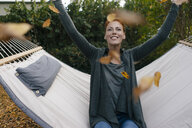 Carefree woman in hammock throwing autumn leaves - JOSF02959