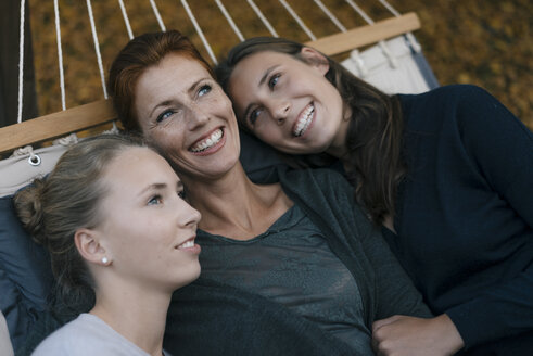 Happy mother with two teenage girls lying in hammock in garden in autumn - JOSF02962