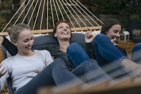 Carefree mother with two teenage girls lying in hammock in garden in autumn - JOSF02965