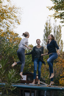 Happy mother with two teenage girls jumping on trampoline in garden in autumn - JOSF02971
