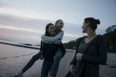 Germany, Hamburg, happy mother with two teenage girls walking on the beach at Elbe shore in the evening - JOSF02977