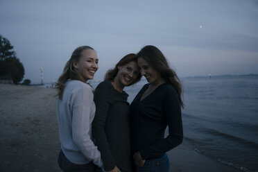 Germany, Hamburg, happy mother with two teenage girls on the beach at Elbe shore in the evening - JOSF02980
