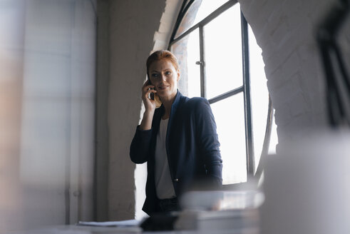 Businesswoman on cell phone at the window in office - JOSF02995