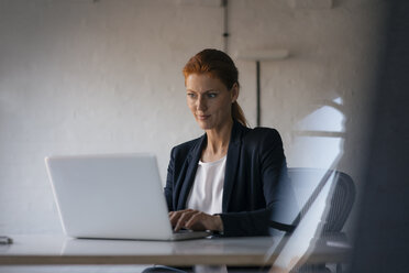 Businesswoman using laptop at desk in office - JOSF02998