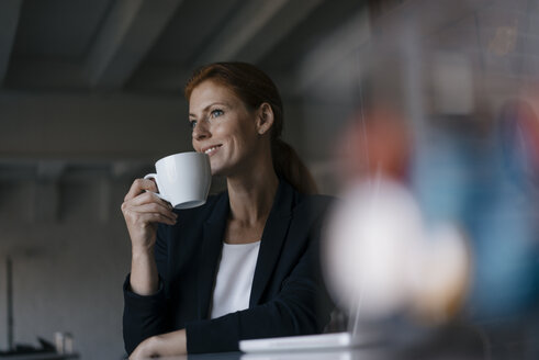 Smiling businesswoman with cup of coffee sitting at desk in office - JOSF03007