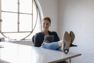 Businesswoman using tablet with feet on desk in office - JOSF03016