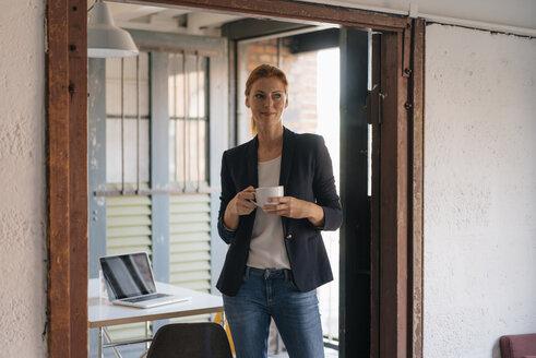 Smiling businesswoman having a coffee break in office - JOSF03019