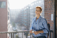 Germany, Hamburg, Speicherstadt, smiling businesswoman with cup of coffee standing at the window with view over the city - JOSF03022