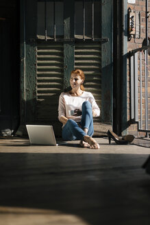 Smiling businesswoman sitting on the floor wth cup of coffee and laptop - JOSF03028