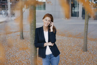 Smiling businesswoman on cell phone outdoors in the city in autumn - JOSF03046