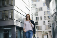 Portrait of smiling businesswoman outdoors in the city - JOSF03049