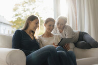Happy mother with two teenage girls using tablet on couch at home - JOSF03052