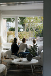Rear view of mother with two teenage girls sitting on couch at home looking out of window - JOSF03058