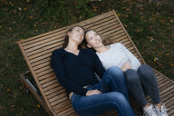 Two affectionate thoughtful teenage girls resting on sun lounger - JOSF03064