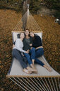 Mother with two teenage girls lying in hammock in garden in autumn - JOSF03067