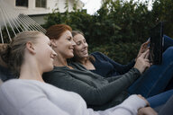 Happy mother with two teenage girls lying in hammock in garden in autumn using tablet - JOSF03070