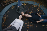 Happy mother with two teenage girls lying on trampoline in autumn - JOSF03073