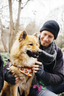 Smiling man looking at Eurasier in park - ASTF02657
