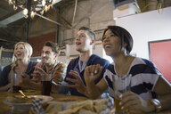 Friends watching sports on TV at brewery - HEROF06624