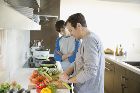 Father teaching son to cook in kitchen - HEROF06669