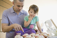 Father and daughter baking cupcakes in kitchen - HEROF06741