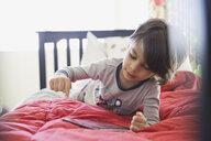 Boy using digital tablet on bed - HEROF06804