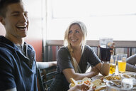 Couple laughing and drinking beer at brewery - HEROF06828