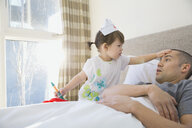Daughter playing nurse to father in bed - HEROF06954