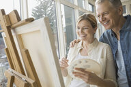 Couple painting at easel in living room - HEROF06987
