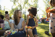 Mother and daughter eating fruit at summer neighborhood block party in park - HEROF06996