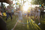 Neighbors spinning in plastic hoops at summer neighborhood block party in sunny park - HEROF07008