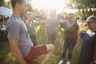 Neighbors playing with hacky sack at summer neighborhood block party in sunny park - HEROF07014