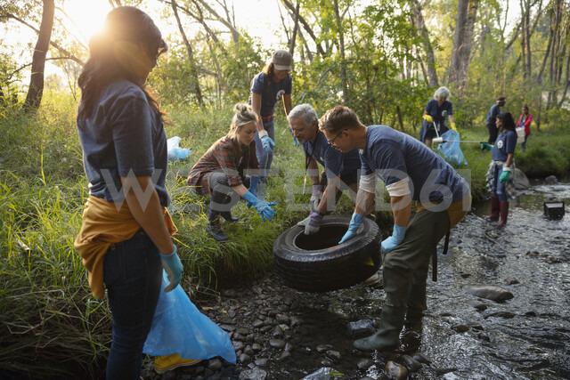 People volunteering, cleaning up garbage and tire in stream - HEROF07059 - Hero Images/Westend61