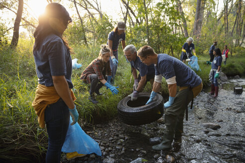 People volunteering, cleaning up garbage and tire in stream - HEROF07059