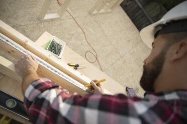 Man measuring wood plank at construction site - HEROF07074